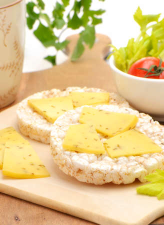 Healthy snack of multigrain rice cakes with spiced gouda cheese in vertical format