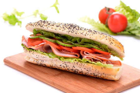 Ham and vegetable submarine sandwich on bamboo cutting board
