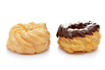 Vanilla and chocolate glazed crullers on white