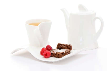 Fresh hot herbal tea with brownies and raspberries on white