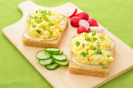 Open face egg salad sandwich with radish and cucumber slices