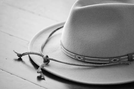 Cowboy hat in black and white on wooden background in horizontal format with selective focus Stock Photo