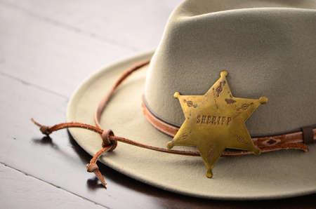 sheriff badge: Sombrero de vaquero con el sheriff insignia en el fondo de madera en formato horizontal con enfoque selectivo