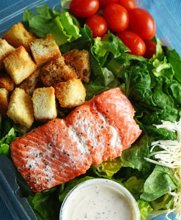 Cold cooked salmon filet with assorted salad ingredients in plastic box ready to go Stock Photo