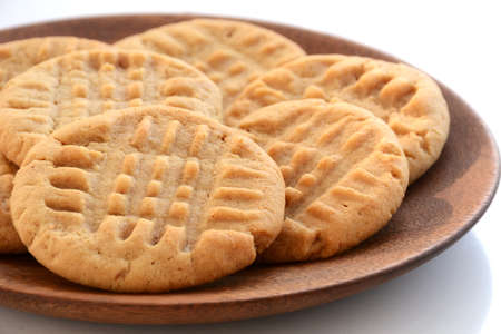 Fresh baked peanut butter cookies on wooden plate shot in natural light with shallow depth of field