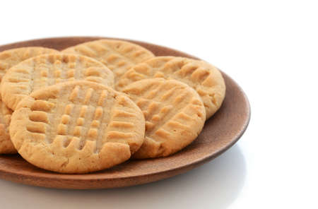 Fresh baked peanut butter cookies on wooden plate shot in natural light with shallow depth of field.  Room for text. Stock Photo