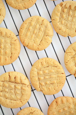 Fresh baked peanut butter cookies cooling on black rack shot from overhead in natural light