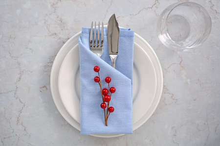 Simple blue and white place setting with red berries shot from overhead in natural light Stock Photo