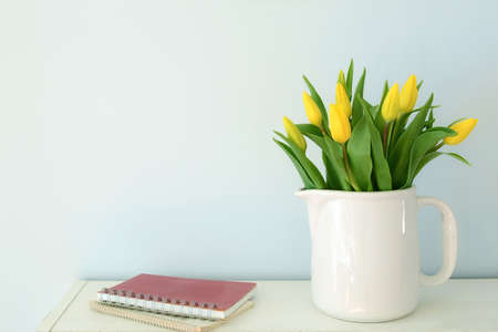 Yellow tulips in white jug on pale blue background in horizontal format with room for text