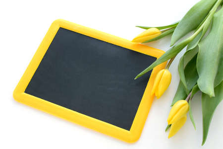 Little yellow framed blackboard with yellow tulips framing one side ready for your Easter or Spring message Stock Photo
