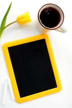 Yellow framed blackboard with coffee and yellow tulip with room for text