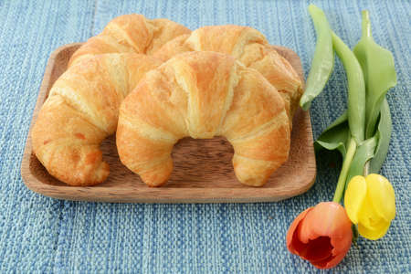 Fresh buttery croissants on rustic wooden plate on blue background