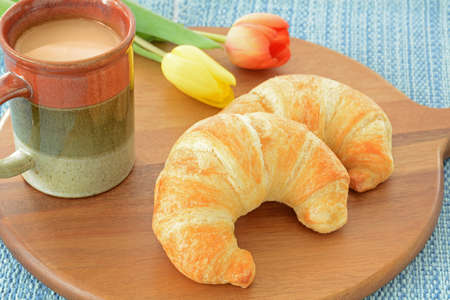 Fresh buttery croissants with tea on rustic wooden board on blue background Stock Photo
