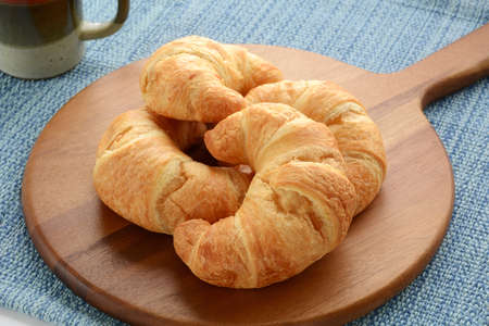 buttery: Fresh buttery croissants with tea on rustic wooden board on blue background Stock Photo
