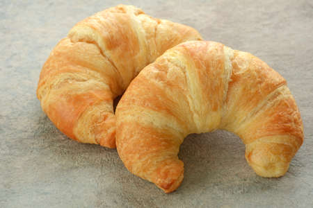 Fresh buttery croissants on rustic tile background