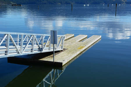 Kayak slips on wooden dock on bay with metal access ramp