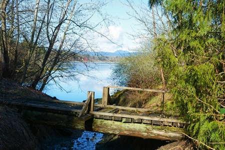 Old wooden footbridge across stream leading into bay