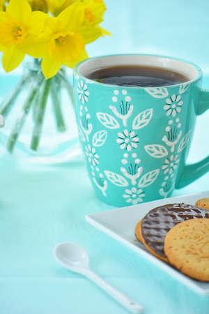 Kleurrijke mok koffie met chocolade bedekte koekjes en gele narcissen in de lentekleuren Stockfoto