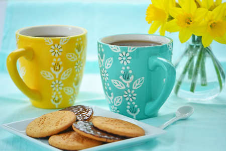 Colorful mugs of coffee with chocolate covered biscuits and daffodils in springtime colors