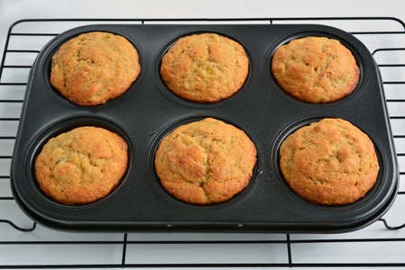 Fresh baked home made banana muffins in muffin tin.  Horizontal format with selective focus on front muffins.