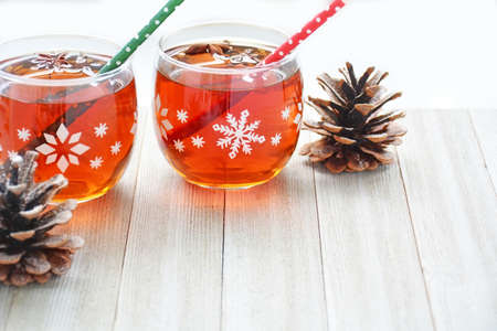Mulled wine in snowflake glasses on rustic board in horizontal format with room for text