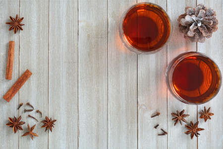 Mulled wine with traditional spices on rustic wooden background in horizontal format with room for text