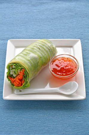 Fresh and healthy avocado salad roll on white plate shot in natural light with room for text