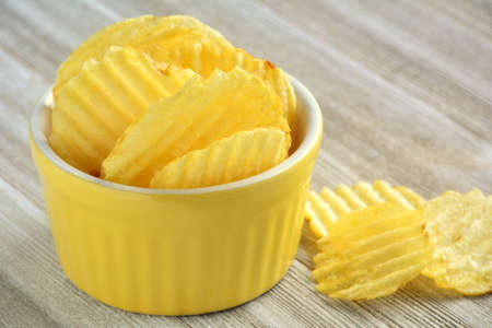 A few ripple ridged potato chips in yellow dish on wooden background.  Selective focus on front chips in dish.  Shot in natural light with room for text.