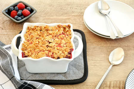 Fresh baked raspberry blueberry crumble for two in small white casserole dish in horizontal format. Delicious fresh seasonal berry dessert.
