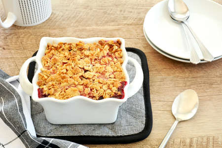 Fresh baked raspberry blueberry crumble for two in small white casserole dish in vertical format.  Delicious fresh seasonal berry dessert. Stock Photo
