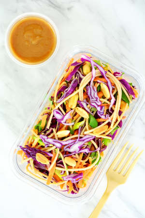 Fresh homemade Thai noodle salad with peanut sauce in meal prep container for take out lunch.  On marble background in flat lay composition.