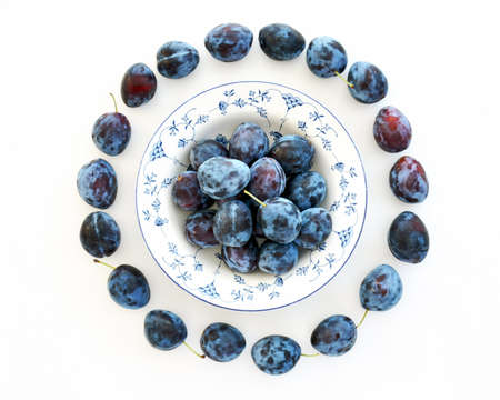 Fresh picked organic prune plums in decorative bowl on white background in flat lay format.  Healthy food concept.