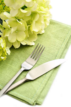 Simple informal place setting with green napkin, hydrangea flowers and stainless steel cutlery on white background. Reklamní fotografie