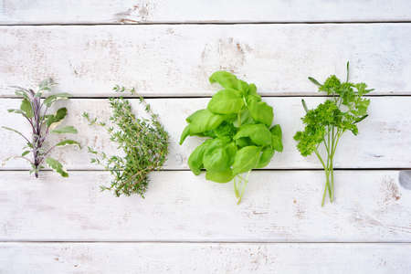 Fresh organic picked herbs on white weathered boards background shot from above. Healthy eating concept, Room for text.