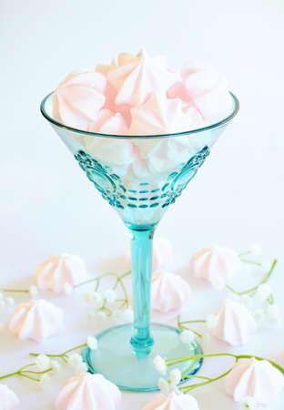 Delicate pink meringue candy kisses in aqua wine glass in vertical format. Selective focus on top meringue.