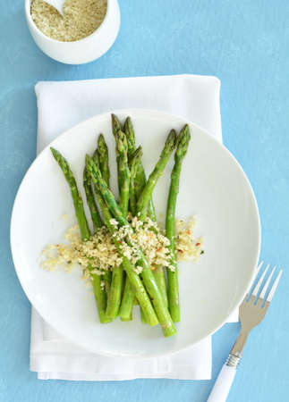 Vibrant green steamed asparagus sprinkled with parmesan, parsley and red pepper flake breadcrumbs.  On white plate on blue background in vertical format.  Flat lay composition.