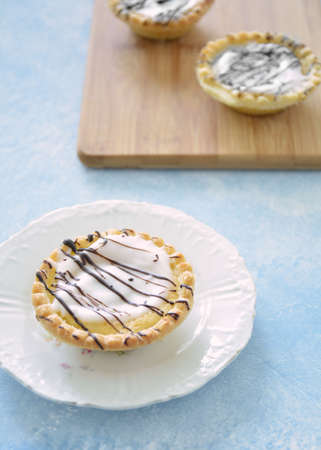 Iced almond tarts with chocolate drizzle on bamboo board and white plate in vertical format. Light blue background.  Selective focus on front tart.