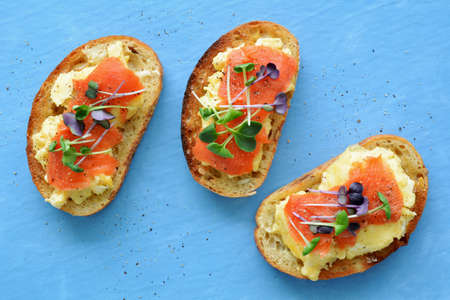 Creamy scrambled egg with smoked salmon and zesty micro greens on herb seed toasts on blue background.  horizontal format in flat lay composition. Shot in natural light.