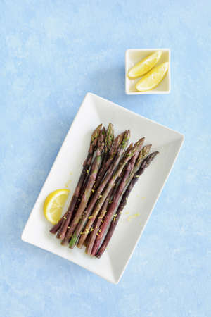 Fresh organic steamed asparagus with lemon slices on white china on blue background in flat lay composition.