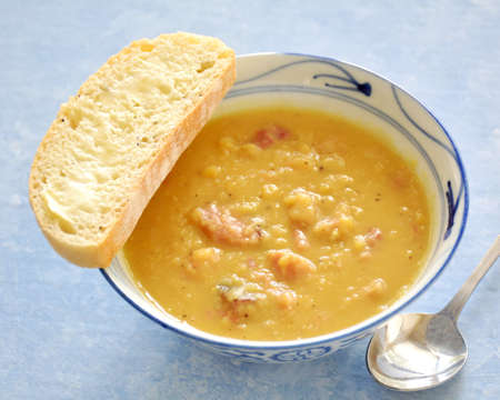 Hearty homemade ham and lentil soup with slice of onion seed cibatta bread on blue background in horizontal format.