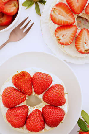 Fresh organic sweet strawberries and cream cheese on plain bagel in vertical format. Selective focus on front strawberries. Reklamní fotografie - 142413689