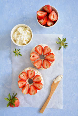 Fresh organic sweet strawberries and cream cheese on plain bagel in vertical format. Selective focus on front strawberries. Flat lay composition.