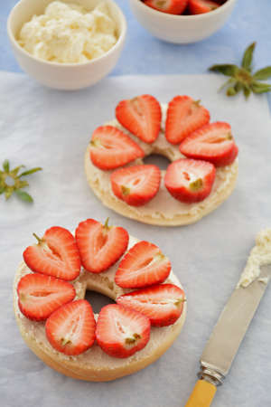 Fresh organic sweet strawberries and cream cheese on plain bagel in vertical format. Selective focus on front strawberries.