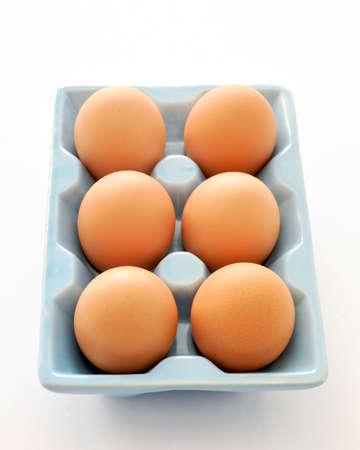 One half dozen farm fresh large brown eggs in blue ceramic tray on white background. Healthy eating concept. Reklamní fotografie - 143075882
