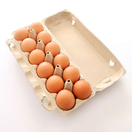 One dozen farm fresh large brown eggs in cardboard carton on white background. Healthy eating concept.