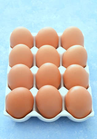 One dozen farm fresh large brown eggs in white ceramic tray on blue background. Healthy eating concept. Reklamní fotografie - 143075885