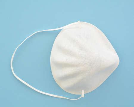 Disposable white paper face mask on blue background.  Medical protection equipment concept. Reklamní fotografie - 143075890