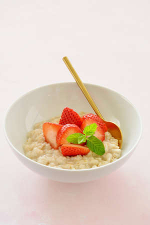 Healthy cooked oatmeal with fresh strawberry slices in white bowl with gold spoon.  Pale pink background in vertical format with room for text.
