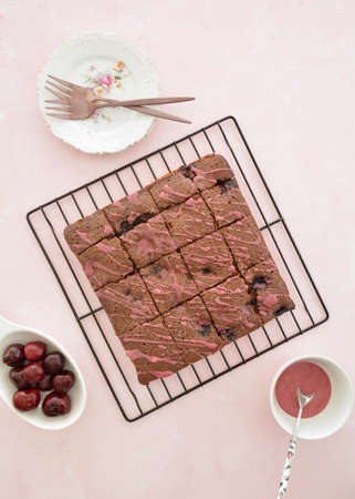 Fresh baked cherry chocolate brownies drizzled with cherry glaze on black cooling rack on pale pink background.  Vertical format in flat lay composition.