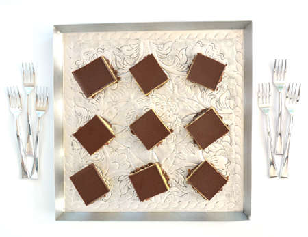 Fresh baked Nanaimo bars on vintage embossed metal tray and tiny forks in flat lay composition. Reklamní fotografie